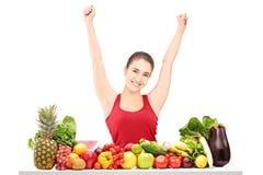 Z podnieceniem młoda kobieta gestykuluje szczęście na stole frui pełno Zdjęcia Stock