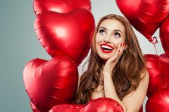 Z podnieceniem młodej kobiety mienie szybko się zwiększać czerwonego serce Zdziwiona dziewczyna z czerwonym wargi makeup, długim  zdjęcie stock