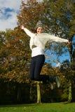 Z podnieceniem młodej kobiety skokowy outside na pięknym jesień dniu Zdjęcie Royalty Free