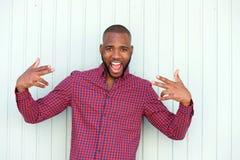 Z podnieceniem młody afrykański mężczyzna gestykuluje rock and roll znaka ścianą Obraz Stock