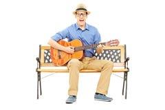 Z podnieceniem młody człowiek bawić się gitarę akustyczną sadzającą na ławce Fotografia Royalty Free