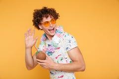 Z podnieceniem młody człowiek trzyma kokosowego koktajl w okularach przeciwsłonecznych Zdjęcie Royalty Free