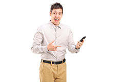 Z podnieceniem młody człowiek wskazuje w kierunku telefonu komórkowego Obrazy Royalty Free