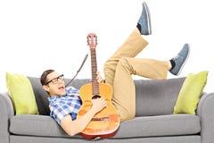 Z podnieceniem młody męski lying on the beach na nowożytnej leżance i bawić się gitarę Zdjęcia Stock