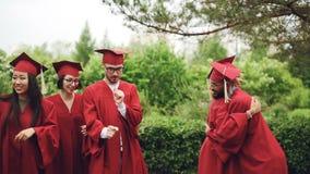 Z podnieceniem młodzi człowiecy i kobieta absolwenci śmia się, robi wysokości pięć, ściska outside i tanczy świętują skalowanie d zbiory