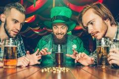 Z podnieceniem młodzi człowiecy siedzą wpólnie przy jeden stołem w pubie Patrzeją złote monety Faceci kubki piwo na stole Mężczyz fotografia royalty free