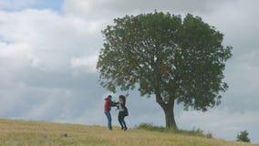 Z podnieceniem młodzi faceci biega w polu wpólnie, trzymający rękę, taniec, skacze zbiory wideo