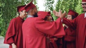 Z podnieceniem młodzi ludzie kończy studia uczni w togach i kapeluszach ściskają gratulujący each inny na skalowaniu, śmia się zdjęcie wideo