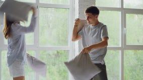 Z podnieceniem młodzi ludzie mają poduszki walkę na dwoistym łóżku, mają zabawy śmiać się i doskakiwanie szczęśliwa para zbiory