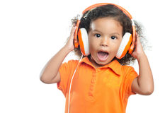 Z podnieceniem mała dziewczynka z afro fryzurą cieszy się jej muzykę na jaskrawych pomarańczowych hełmofonach Obrazy Stock
