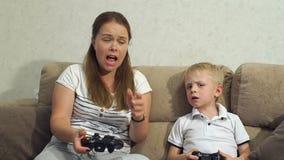 Z podnieceniem matka i syn bawić się gra wideo wpólnie w domu zdjęcie wideo