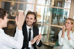 Z podnieceniem partnery biznesowi oklaskuje gratulowanie kolegi wi obraz stock