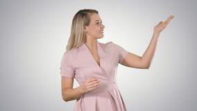 Z podnieceniem piękna młoda kobieta w menchii smokingowy opowiadać kamera na gradientowym tle obrazy royalty free