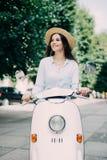 Z podnieceniem potomstwa i pięknej kobiety jeździecka hulajnoga wzdłuż ulicy obraz stock