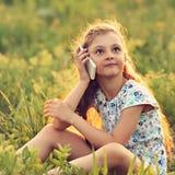 Z podnieceniem poważny śliczny dzieciak dziewczyny obsiadanie na szkle, opowiada na m Fotografia Stock