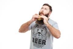 Z podnieceniem przystojny mężczyzna z brody łasowania cieszyć się i hamburgerem fotografia royalty free