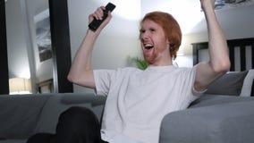 Z podnieceniem rudzielec mężczyzna reaguje sukces, ogląda tv fotografia stock