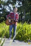 Z podnieceniem 40s mężczyzna bawić się gitarę w odprowadzeniu w miasto parku Obrazy Royalty Free