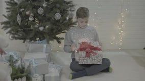 Z podnieceniem szczęśliwy chłopiec otwarcia bożych narodzeń teraźniejszości prezenta pudełko w dekorującym nowy rok atmosfery drz zbiory