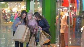 Z podnieceniem, szczęśliwy shopaholics, dziewczyny, przyjaciele pokazuje innych torba na zakupy w centrum handlowym each zdjęcie wideo