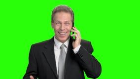 Z podnieceniem wzmacniający dojrzały mężczyzna opowiada na telefonie zbiory