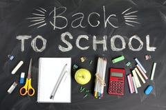 ` Z powrotem szkoły ` ręcznie pisany z szkolnymi dostawami na czarnym tle Odgórny widok zdjęcia royalty free