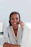 Z słuchawki klienta uśmiechnięty etniczny agent dalej fotografia stock