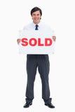 Z sprzedającym znakiem uśmiechnięty męski agent nieruchomości Obrazy Royalty Free
