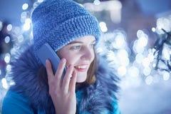 Z ukosa portret piękna młoda kobieta jest ubranym modnego zima kapelusz i kurtka rozmowę telefoniczną plenerową, pozy przeciw c obrazy stock
