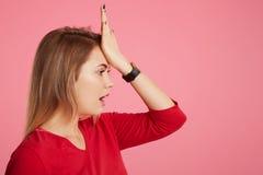 Z ukosa portret zapominalska kobieta pamięta coś znacząco, utrzymanie ręka na czole, pozy przeciw różowemu tłu z policjantem zdjęcie stock