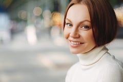 Z ukosa strzał przyjemna przyglądająca kobieta z uzupełnia, oferta uśmiech, ubierający w białym turtleneck pulowerze przeciw zama zdjęcia stock