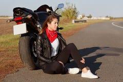 Z ukosa strzał zadumany młody doświadczony żeński rowerzysta jest ubranym skórzaną kurtkę, biali sneakers, siedzi blisko motocykl obrazy royalty free