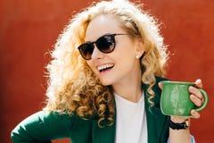 Z ukosa zakończenie jest ubranym eleganckich cienie i kurtki mienia zieleni filiżankę herbata ma szczerego uśmiech na jej twarzy  obraz royalty free