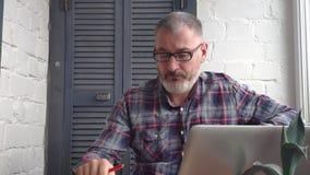Z włosami brodaty męski księgowy pracuje w domu za laptopem, robi raportowi przeciw tłu minimalistyczny wnętrze zdjęcie wideo