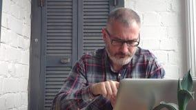 Z włosami brodaty męski księgowy pracuje w domu za laptopem, robi raportowi przeciw tłu minimalistyczny wnętrze zbiory