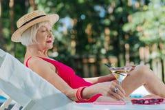 Z włosami dojrzała kobieta jest ubranym słomianego kapeluszu lying on the beach blisko basenu obraz stock