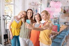 Z włosami kobieta jest ubranym żółtą bluzkę robi fotografii z przyjaciółmi obraz stock