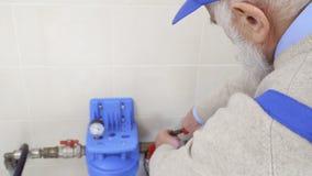 Z włosami pracownik odplata dokrętki na ogrzewanie drymbie zbiory