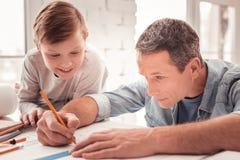 Z włosami syn ogląda jego ojca rysunku postacie dla geometrii klasy zdjęcia royalty free