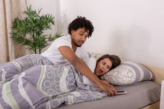 Z zazdrością chłopak patrzeje dziewczyny dzwoni w sypialni obrazy stock