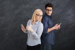 Z zazdrością dziewczyny dopatrywania chłopiec texting na telefonie obrazy stock