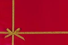 Z złocistym faborkiem prezenta czerwony tło Obrazy Royalty Free