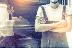 Załatwiać samochodowego silnika w samochód naprawy garażu przystojny mechanik obrazy stock