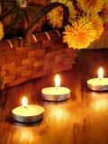 Zaświecać świeczki i łozinowy kosz z banią i kwiatami w tle Obraz Royalty Free