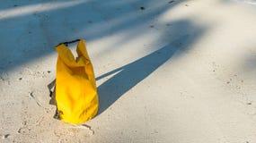 Zaświeca i ocienia na piaskowatej plaży z żółtą wodoodporną torbą Zdjęcia Royalty Free