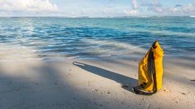 Zaświeca i ocienia na piaskowatej plaży z żółtą wodoodporną torbą Obrazy Stock