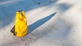Zaświeca i ocienia na piaskowatej plaży z żółtą wodoodporną torbą i h Zdjęcie Royalty Free