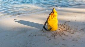 Zaświeca i ocienia na piaskowatej plaży z żółtą wodoodporną torbą i h Obraz Royalty Free