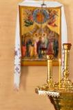 Zaświecająca świeczka i dwa candlesticks przed orthodoxal ikoną na żółtym tle obrazy stock