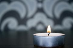 zaświecająca świeczka na stole Obrazy Stock
